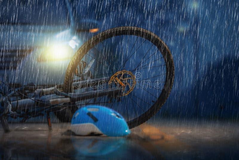 Choque de coche del accidente con la bicicleta en tiempo lluvioso imagen de archivo
