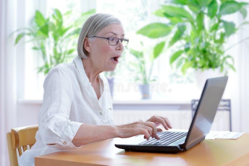 Choque mayor del ordenador portátil de la mujer sorprendido imagen de archivo libre de regalías