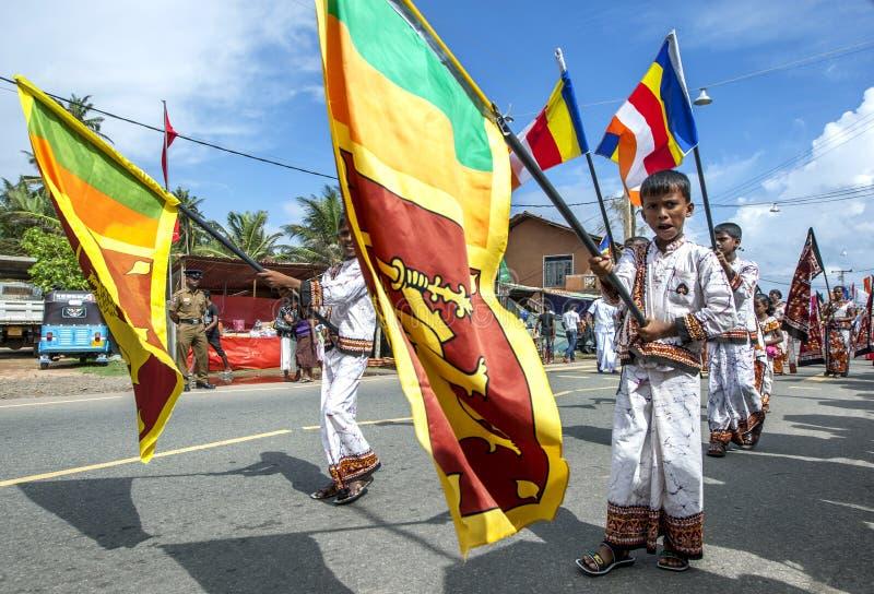 Chorągwiani okaziciele niesie lankijczyka zaznaczają podczas Hikkaduwa Perahara obraz stock