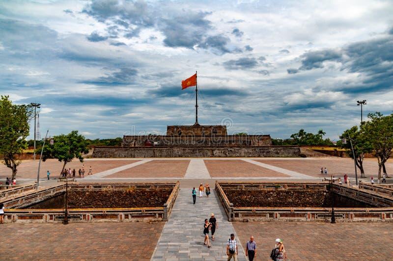 Chorągwiany wierza w odcieniu, Wietnam, z dramatycznymi chmurami i turystami w forground fotografia royalty free