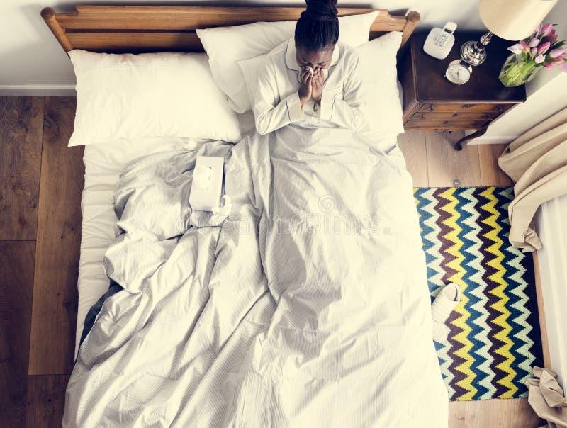 Chora amerykanin afrykańskiego pochodzenia kobieta na łóżkowym dmuchaniu jej nos zdjęcie stock
