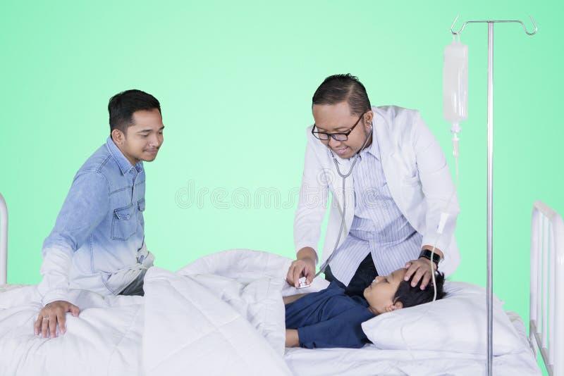 Chora chłopiec egzamininująca jego lekarką na studiu fotografia stock