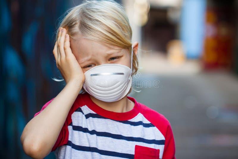 Chora chłopiec jest ubranym twarzy maskę fotografia stock