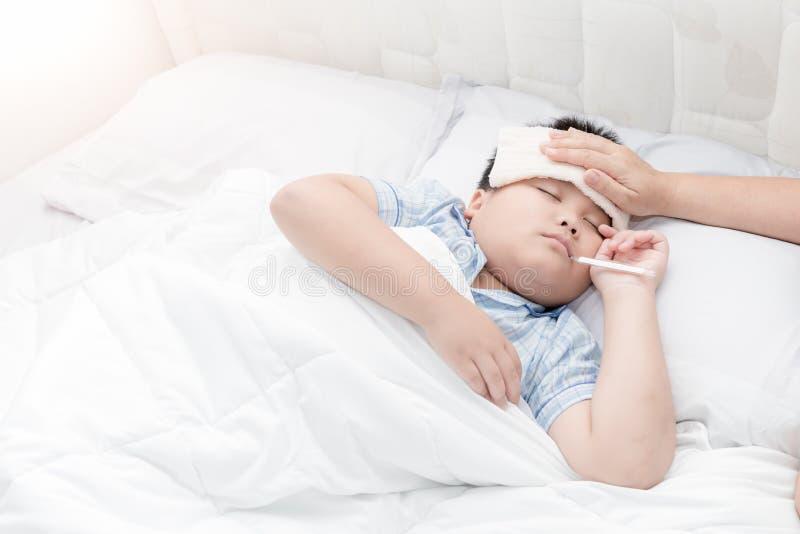 Chora chłopiec kłaść w łóżku z termometrem i matka wręczamy brać t obraz royalty free