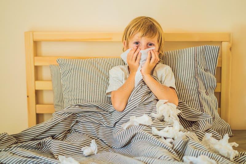 Chora chłopiec ka jego nos z wytarciami i wyciera Chory dziecko z febr? i chorob? w ? zdjęcia royalty free