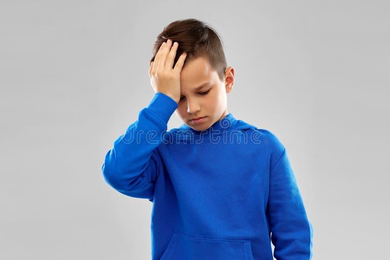 Chora chłopiec w slue hoodie cierpieniu od migreny zdjęcia royalty free