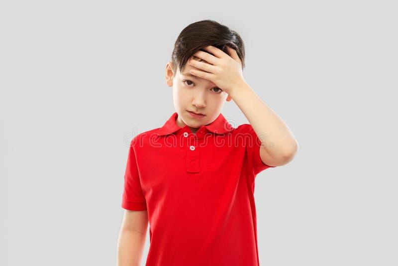 Chora ch?opiec w czerwonym koszulki cierpieniu od migreny obrazy royalty free