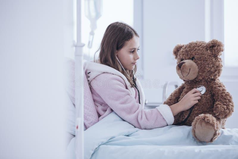 Chora dziewczyna egzamininuje misia w szpitalu z stetoskopem obraz royalty free