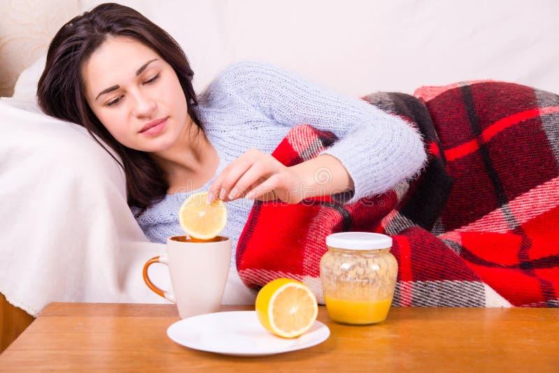 Chora dziewczyna pod koc taktował herbaty z cytryną zdjęcia royalty free