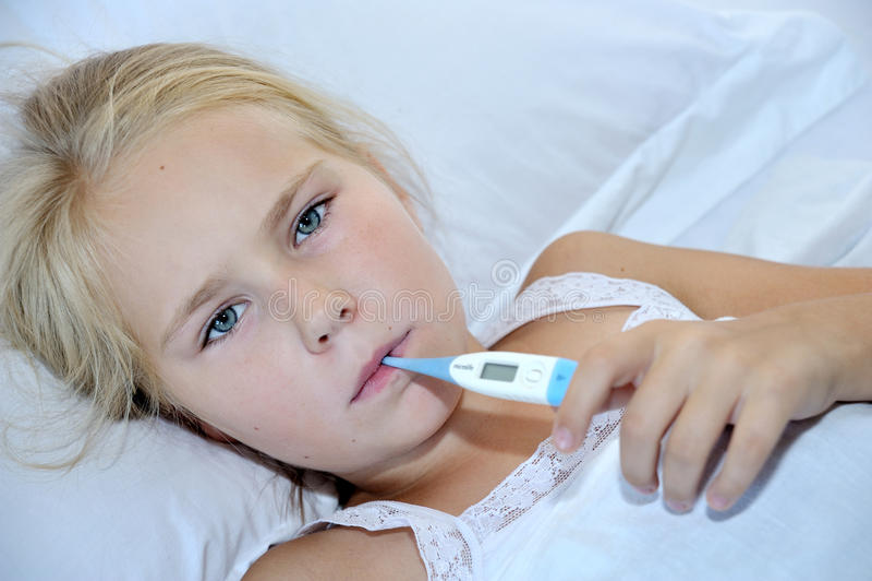 Chora dziewczyna z termometrem w usta lying on the beach na łóżku zdjęcia stock