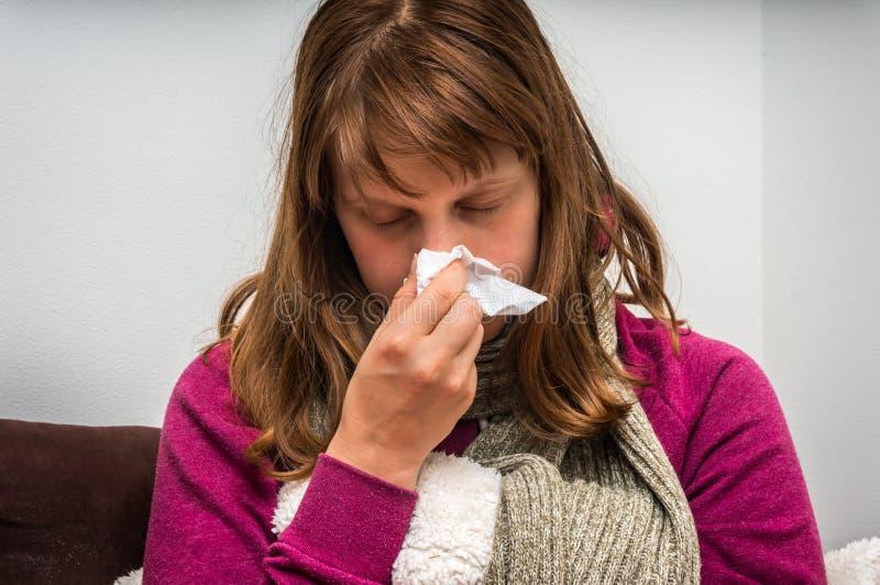 Chora kobieta ma grypę i kicha w chusteczkę obraz royalty free
