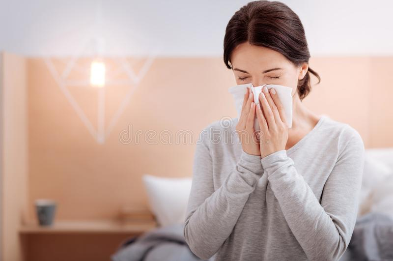 Chora kobieta siedzi w domu i kicha zdjęcie royalty free