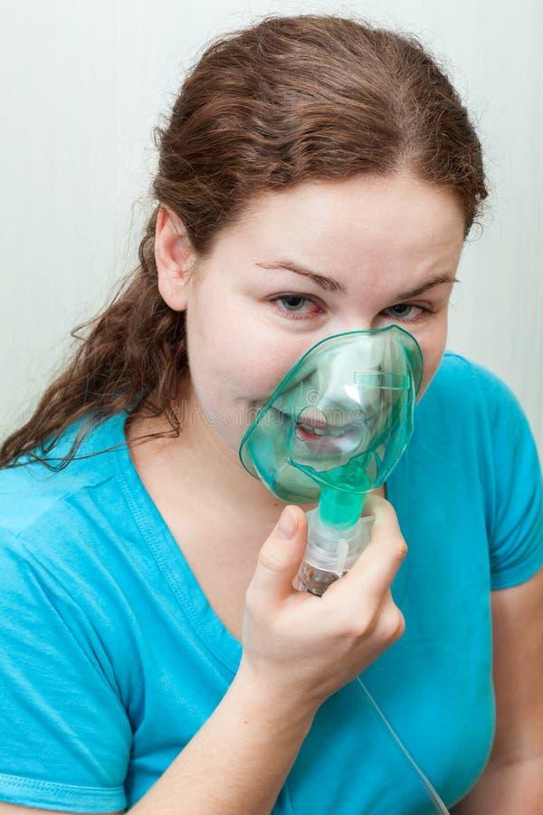 Chora kobieta z bolesnym gardłem robi inhalaci z maską na jej twarzy Nebulizer przyrząd fotografia stock