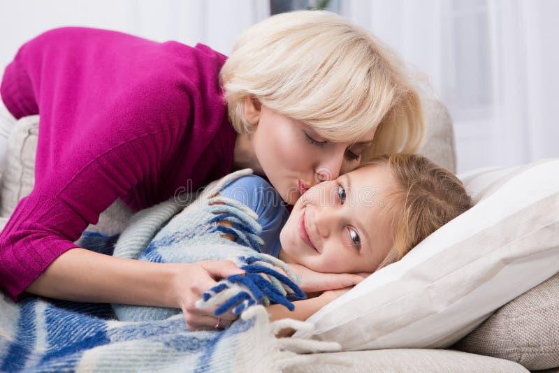 Chora mała dziewczynka zostaje w domu, mama całuje ona zdjęcie stock