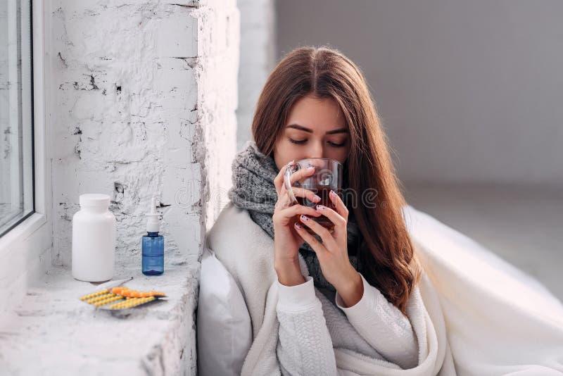 Chora niezdrowa kobieta pije rozgrzewkowego napój indoors zimna drobiu Zbliżenie piękna młoda dziewczyna z gorącą filiżanką herba obrazy royalty free