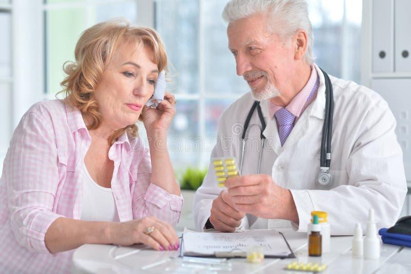 Chora starsza kobieta w doktorskim ` s biurze obraz stock