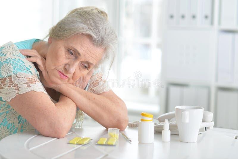 Chora starsza kobieta z lekarstwem obraz stock