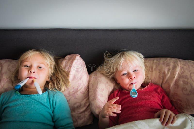 Chore dziewczynki z termometrem leżącym w łóżku obraz royalty free