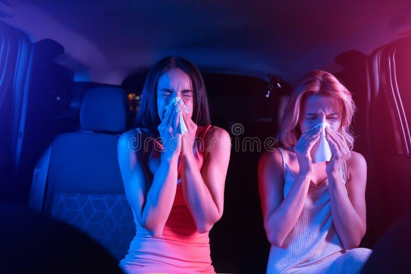 Chore dziewczyny siedzą w samochodzie i dmuchaniu w suchej pielusze Ich nosy biegają Dziewczyny cierpią Dziewczyny są obrazy royalty free