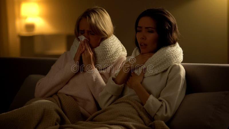 Chore kobiety kłama w łóżku, kichnięciu i mieniu w szalikach, grypowy wirus zdjęcia stock