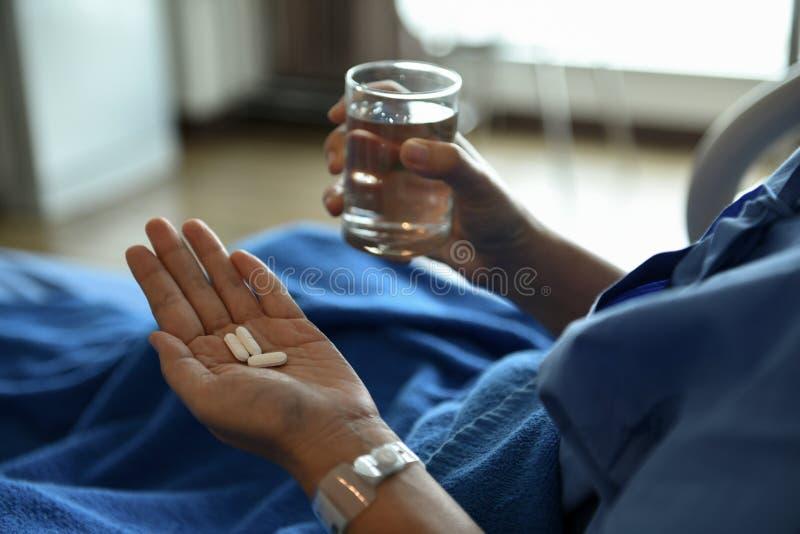 Chore kobiety siedzą na łóżku Medycynę i szkło woda w jej ręce fotografia royalty free