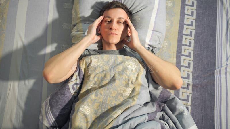 Chore mężczyzny nacierania świątynie na łóżku obrazy stock