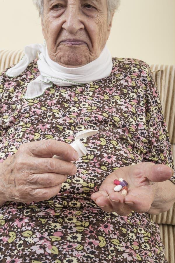 Chore starsze kobiety mienia pigułki na palmie fotografia stock