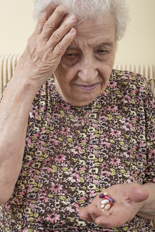 Chore starsze kobiety mienia pigułki na palmie obraz royalty free