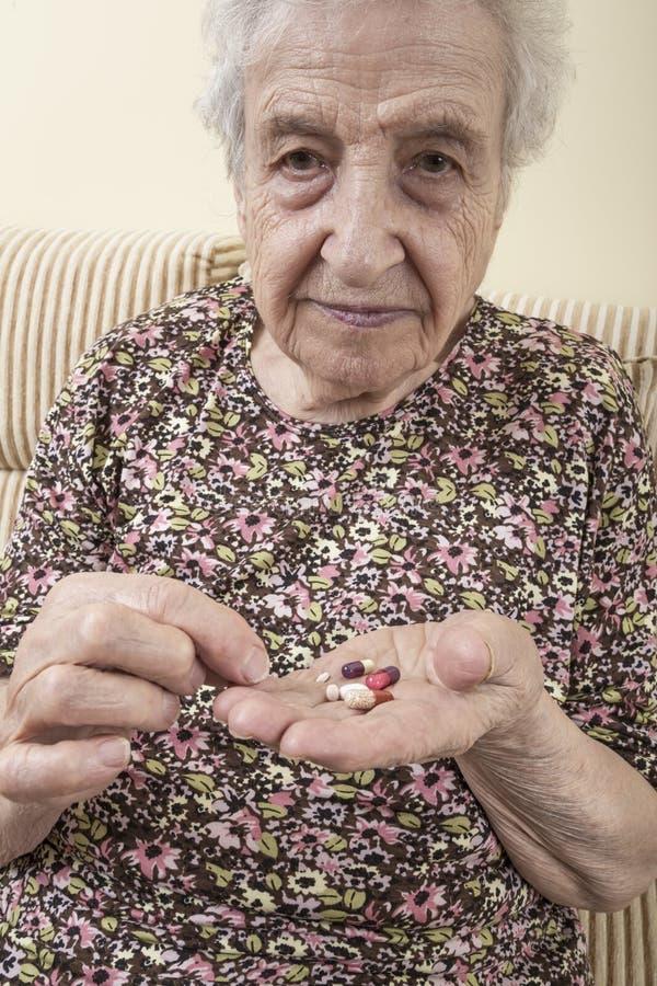 Chore starsze kobiety mienia pigułki na palmie fotografia royalty free