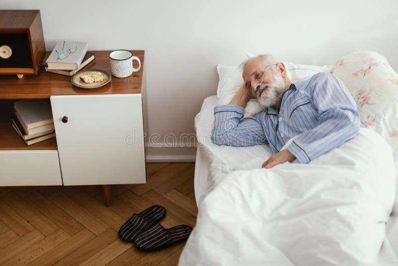 Chore starsze osoby obsługują być ubranym błękitnego piżamy lying on the beach w łóżku przy karmiącym domem fotografia stock