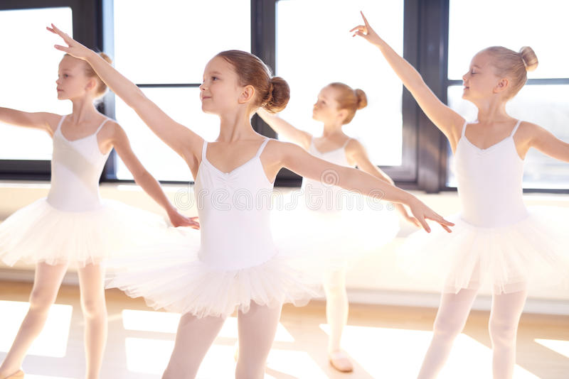 Choreographed dance by a group young ballerinas. Choreographed dance by a group of graceful pretty young ballerinas practicing during class at a classical ballet stock photography