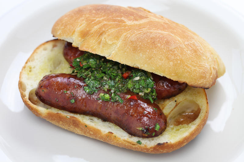 Choripan, close up. Chorizo hot dog with chimichurri sauce, Argentine food, close up royalty free stock image