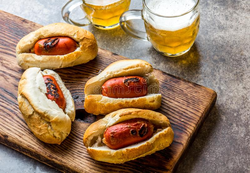 Choripan. Latin American Argentine and chilean food. Grilled chorizo sausages hot dogs served with beer, top view, stone. Choripan. Latin American Argentine and stock image
