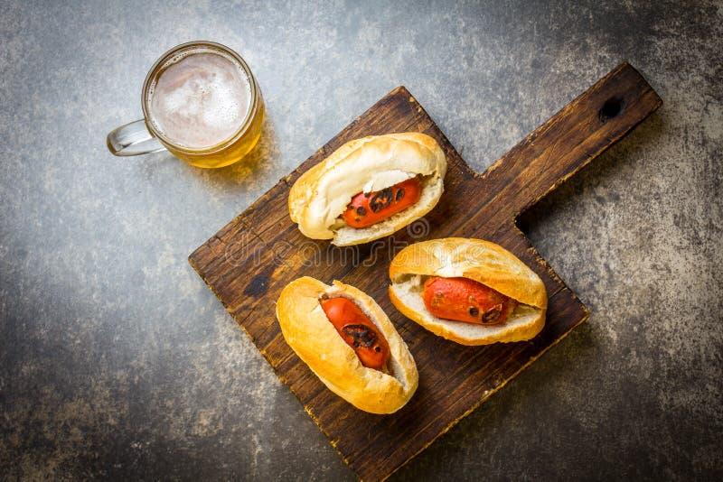 Choripan Latin - amerikansk argentinare- och chilenaremat Grillade chorizokorvvarmkorvar tjänade som med öl, den bästa sikten, st arkivfoto