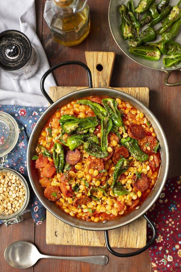 Chorizoen och gula torkade delade ärtor låter småkoka med tomater och padronespeppar arkivfoton
