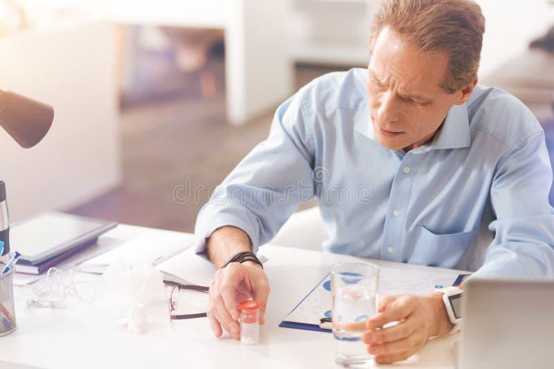 Choroba dojrzały męski urzędnik bierze pigułki zdjęcie royalty free
