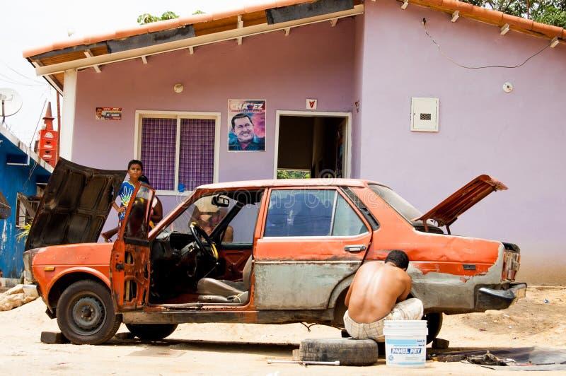 Choroni, Венесуэла - 20-ое июля 2018: семьянин пробуя отремонтировать его автомобиль в плохом доме сельской местности, с его деть стоковое изображение rf