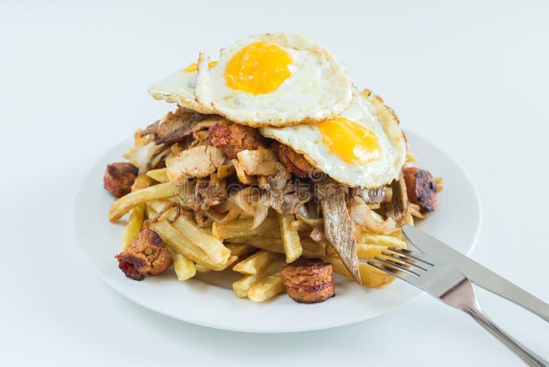 Chorrillana, batatas fritas, cebola fritada, salsichas e ovos fritos com fundo branco imagem de stock