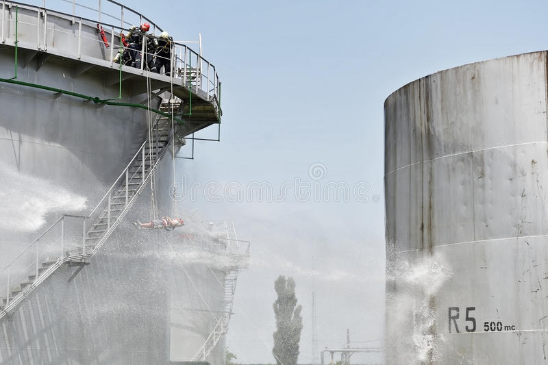 Chorro de agua del bombero en el tanque de almacenamiento grande imagen de archivo libre de regalías