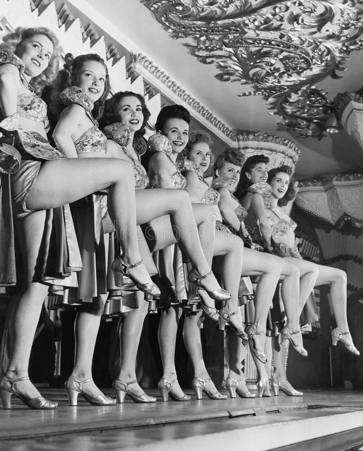 Chorus line of women with legs lifted stock photography