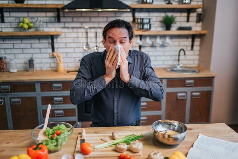 Chory dorosły mężczyzna kicha biała pielucha Stoi przy stołem w kuchni Biurko pełno kolorowi zdrowi warzywa i obraz royalty free
