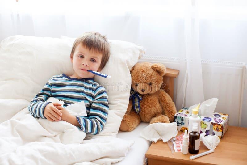 Chory dziecko chłopiec lying on the beach w łóżku z febrą, odpoczywa zdjęcia stock
