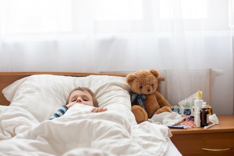 Chory dziecko chłopiec lying on the beach w łóżku z febrą, odpoczywa obrazy stock