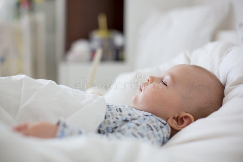 Chory dziecko chłopiec lying on the beach w łóżku z febrą, odpoczywa w domu obraz royalty free