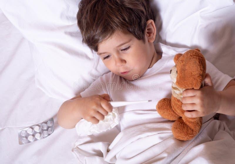 Chory dziecko z febrą i chorobą w łóżkowej sprawdza temperaturze z termometrem Żartuje grypowych traktowania wszystkie poj?cia ub obraz royalty free