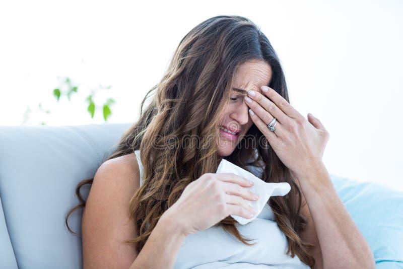 Chory kobieta płacz na kanapie zdjęcia stock