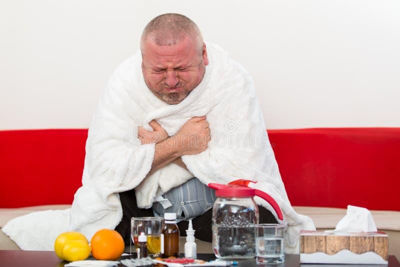 Chory mężczyzna jest ubranym piżamy cierpienia zimy i zimna grypowego wirusa ma medycynę obrazy royalty free