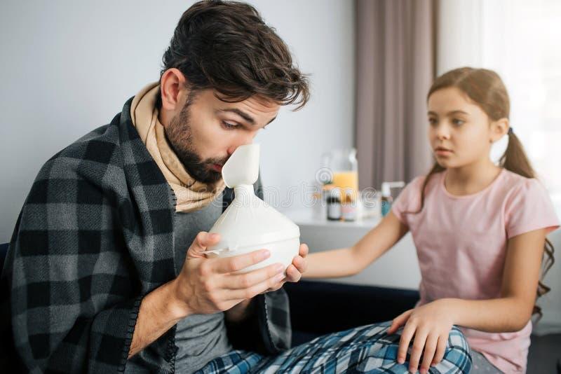 Chory młody człowiek robi inhalacyjnym procedurom Trzyma specjalnego wyposażenie fo to Zmartwiona mała dziewczyna siedzi oprócz o obraz stock
