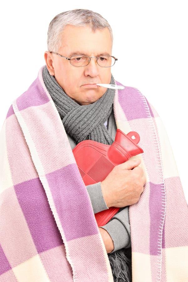 Chory senior z termometrem w jego usta, zakrywającym z koc fotografia stock