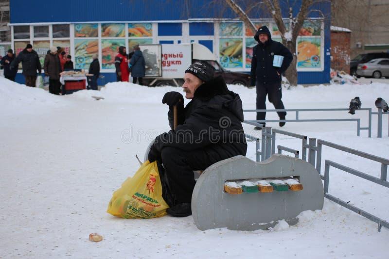 Chory starego człowieka mężczyzna męczył obsiadanie na ławce w zimie zdjęcia royalty free
